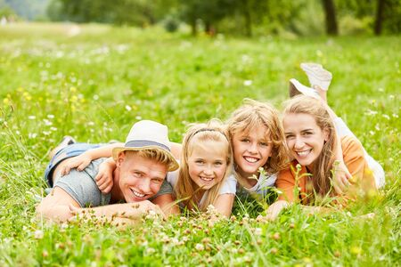 Happy family is lying together on a meadow in the summer
