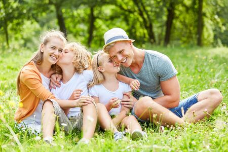 Happy family and two children is sitting relaxed in nature