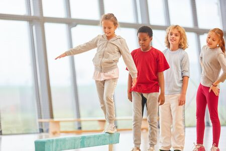 Sporty students balance on a balance beam in physical education Stock Photo