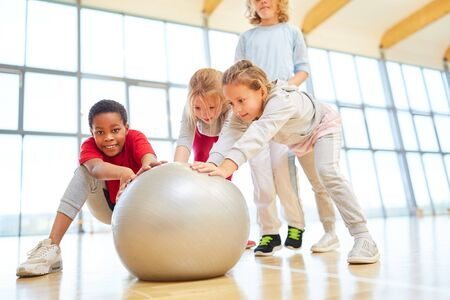 Group of kids in the gym in physical education with gym ball or bouncy ball