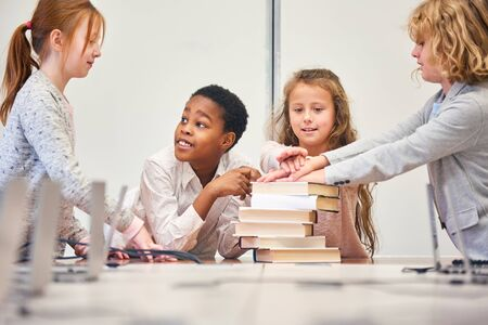 Children as students of a learning group stack their hands for the team spirit