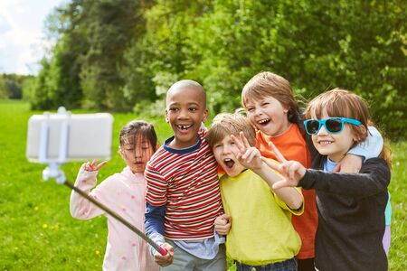 Group of kids is having fun together while making selfie with smartphone on selfie stick