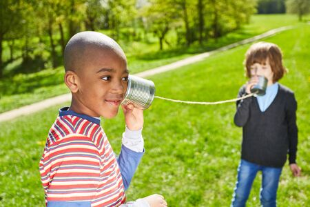 Two children use the telephone on the phone during their summer vacations in the park