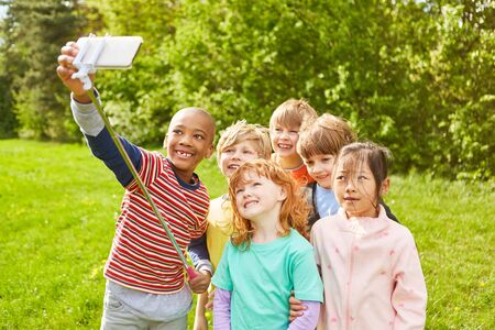 Group of kids is having fun and taking a selfie together with smartphone and selfie stick