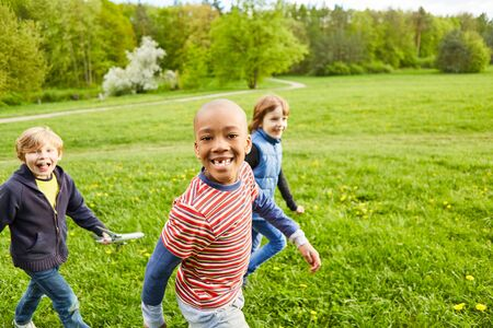 Children as friends play together on a meadow in the park on a children's birthday party Stock Photo