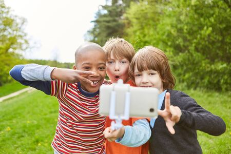 Three kids go nuts and take a selfie with their smartphone on the Selfie Stick Imagens - 134714827