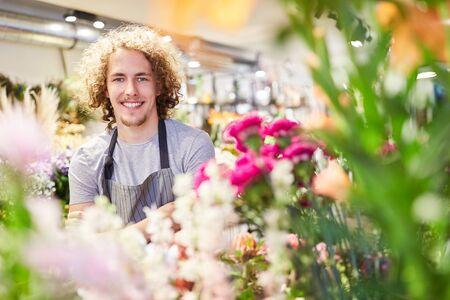 Smiling florist between colorful cut flowers in his flower shop