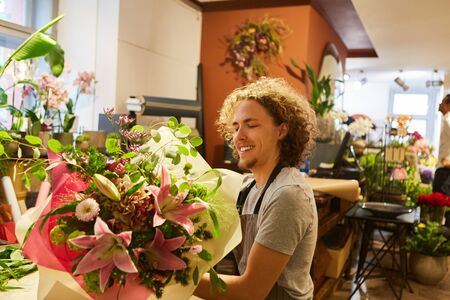 Young man as florist wraps bouquet in paper in flower shop