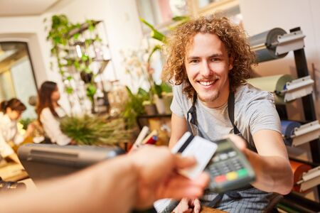 Customer pays by credit card at the cashier in the garden center