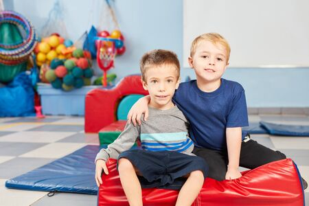 Two guys as good friends in the gym of a preschool or kindergarten