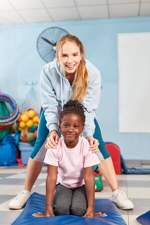 Cheerful sports teacher or kindergarten teacher together with a girl doing gymnastics Stock Photo