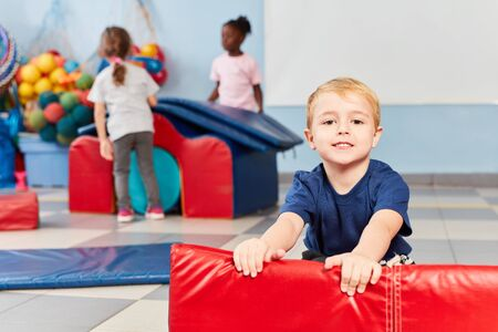 Smiling boy in the gym in kindergarten or preschool while playing