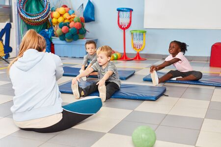 Group of kids is doing exercise to stretching in the gym in kindergarten or preschool Stock Photo