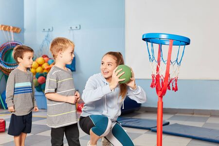 Sports teacher and children play basketball together in the gym of preschool