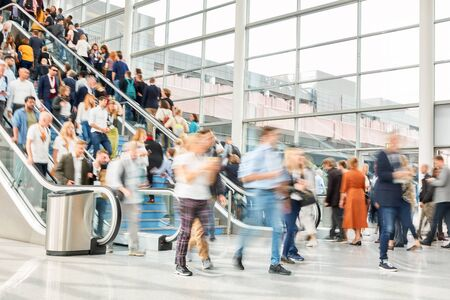 Many anonymous people on escalator and stairs of a trade fair Stock Photo