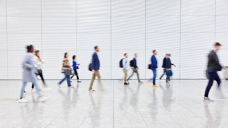 Anonymous blurred crowd of business people walks by gear on a trade fair or in an airport