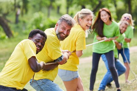 Young people enjoy tug of war as an exercise in the team building workshop