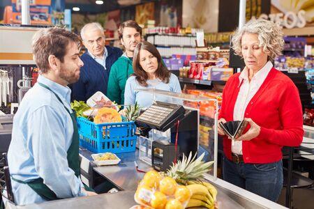 La donna anziana che paga alla cassa del supermercato guarda nel suo portafoglio