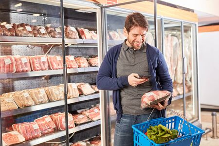 Man scans a meat product with smartphone app while shopping in supermarket