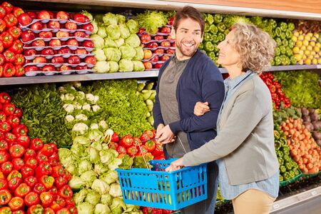 Smiling couple in front of a shelf with big vegetables Assortment in supermarket