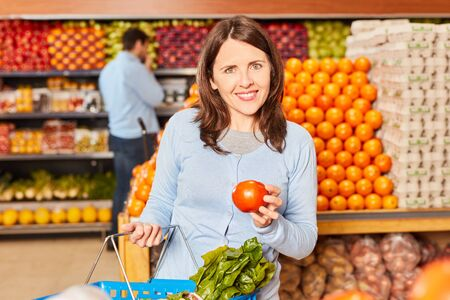 Young woman is holding a healthy organic tomato in hand in the vegetable section