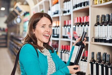 Woman is happy buying a bottle of red wine in the supermarket or wine shop