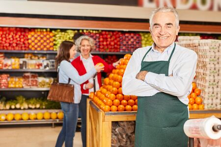Senior as a successful salesman with crossed arms in the supermarket