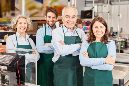 Group of smiling salesmen with market manager and trainee at supermarket checkout