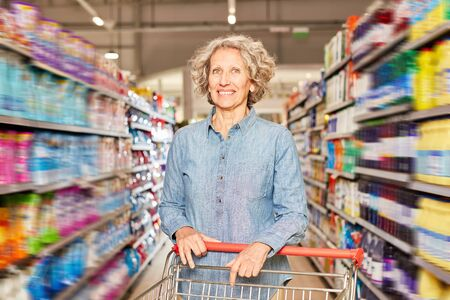 Smiling senior woman as a customer in the supermarket or discount store with shopping cart