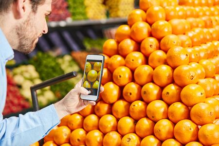 Man as a customer with smartphone app in the fruit department in the supermarket Zdjęcie Seryjne