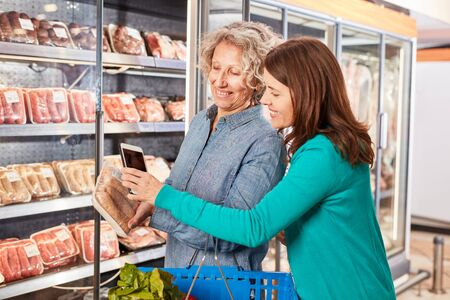 Women use smartphone app to scan a pack of meat in the supermarket