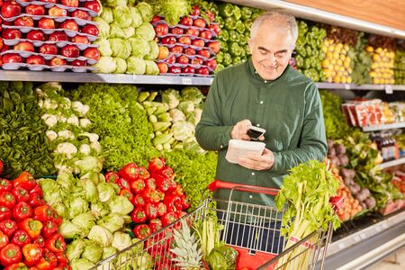 Senior man with shopping cart and smartphone while scanning food