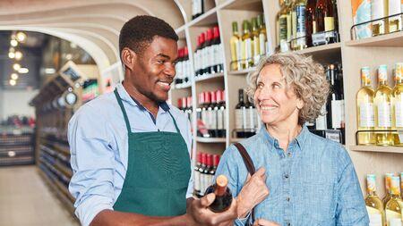 Customer gets advice on buying red wine from African salesman Zdjęcie Seryjne