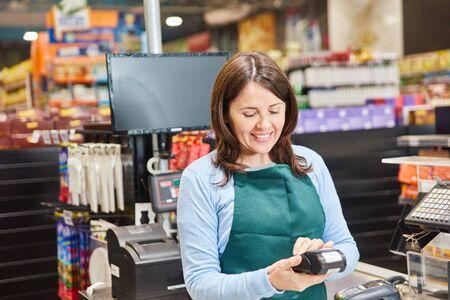 Femme souriante en tant que caissière avec un scanner de codes-barres à la caissière du supermarché