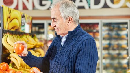 Senior man as a customer or consumer while shopping vegetables at the supermarket