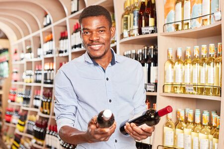African man as a customer with two bottles of wine in the wine shop or supermarket