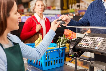 Customer pays with credit card or customer card at checkout in the supermarket