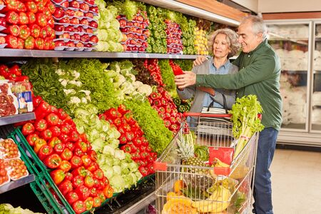 Senior couple with shopping cart together while buying vegetables in supermarket