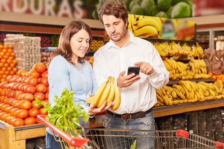 Young couple buying bananas in the supermarket uses smartphone app Zdjęcie Seryjne
