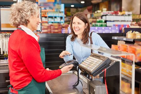 Young woman makes mobile payment with NFC smartphone at supermarket checkout