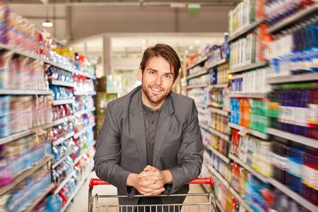 Satisfied man as a customer in the supermarket or discounter between shelves