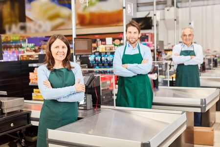 Three salesmen in green apron at the supermarket cashier with crossed arms