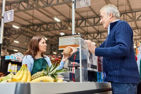 Senior as a customer paying at checkout in the supermarket or discounter Zdjęcie Seryjne