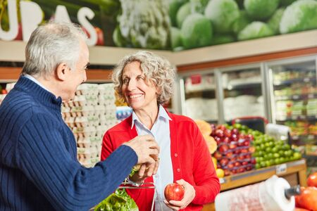Seniors buying vegetables and fruits in vegetable department in the supermarket