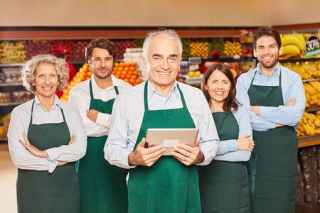 Friendly senior as a market leader with sales team and trainee in the supermarket