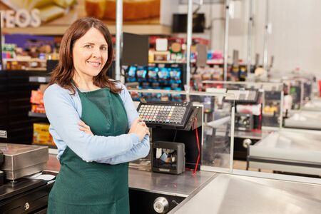 Woman in green apron as a cashier at the cash register in the supermarket or discounter