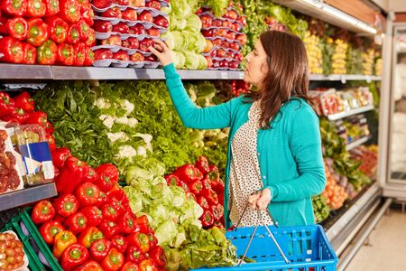Young woman with shopping basket while buying organic vegetables for healthy eating Zdjęcie Seryjne