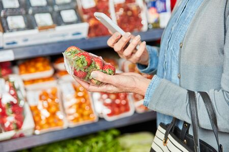Customer scans pack of strawberries with the smartphone app for product comparison Фото со стока