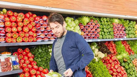 Man as a customer at the vegetable shopping in the vegetable department in the supermarket Zdjęcie Seryjne