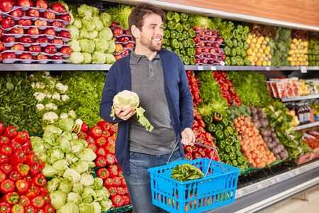 Young man as customer with shopping basket while buying vegetables in supermarket